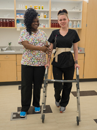 Two female Health Services students with a walker