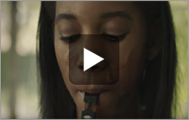 Teen female vaping with negative effects shown on her face