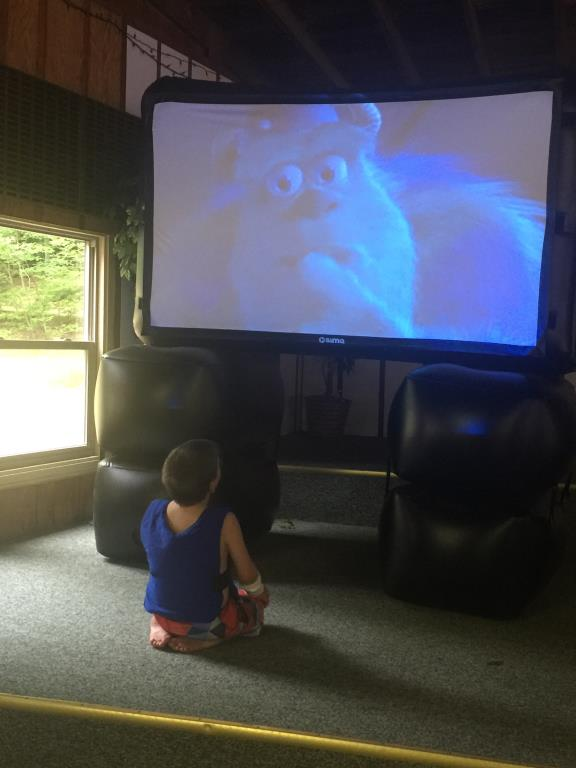 little boy watching movie on a projector screen